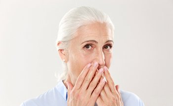 older woman embarrassed covering mouth