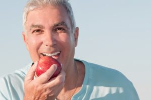 older smiling holding red apple