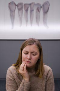 Woman in pain at emergency dentist in San Antonio.